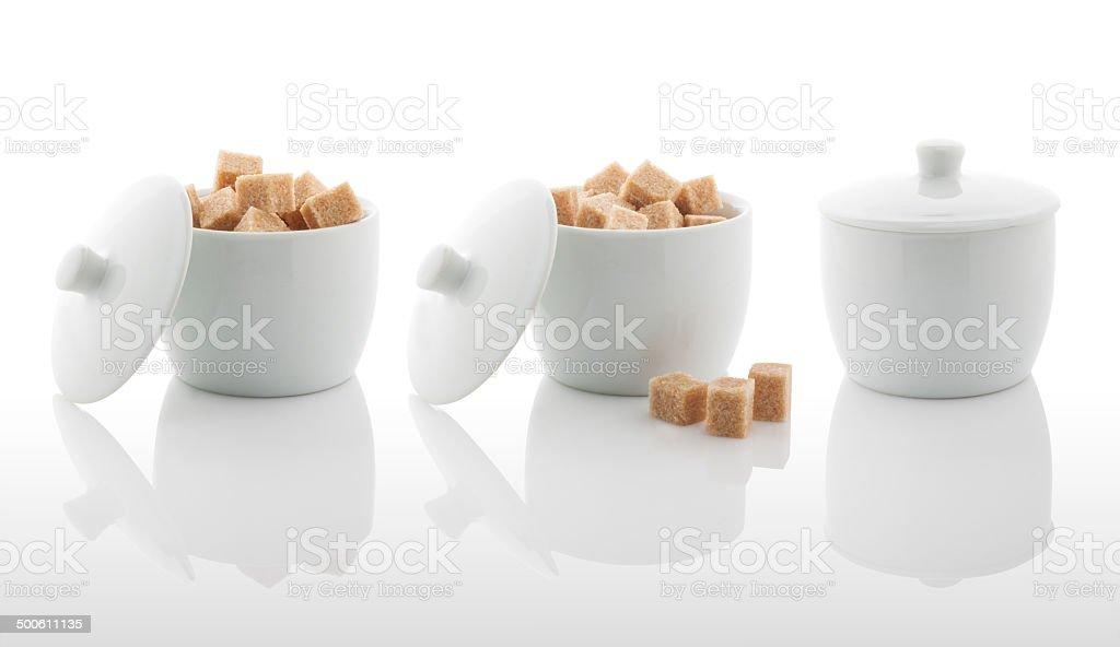 White sugar bowl and brown sugar cubes stock photo