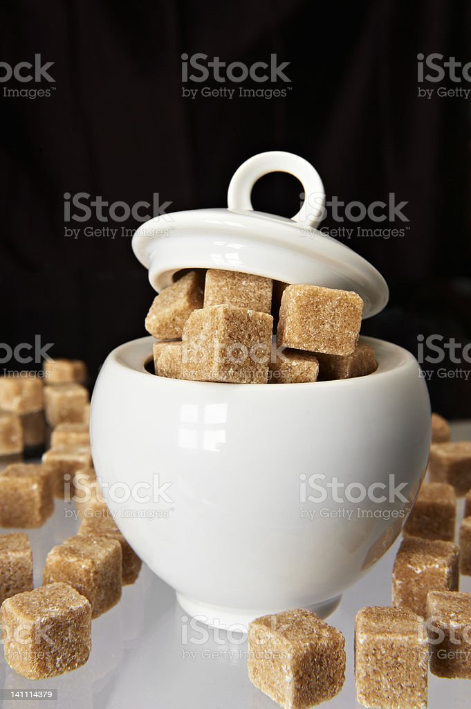 White sugarbowl with brown sugarcubes royalty-free stock photo