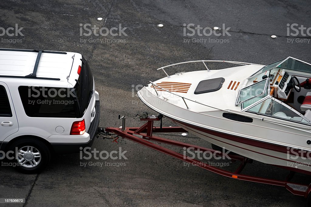 White SUV pulling white speed boat on trailer from above stock photo