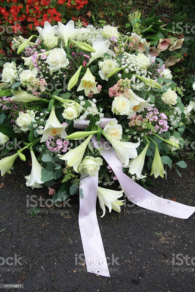 White sympathy flowers near a grave royalty-free stock photo