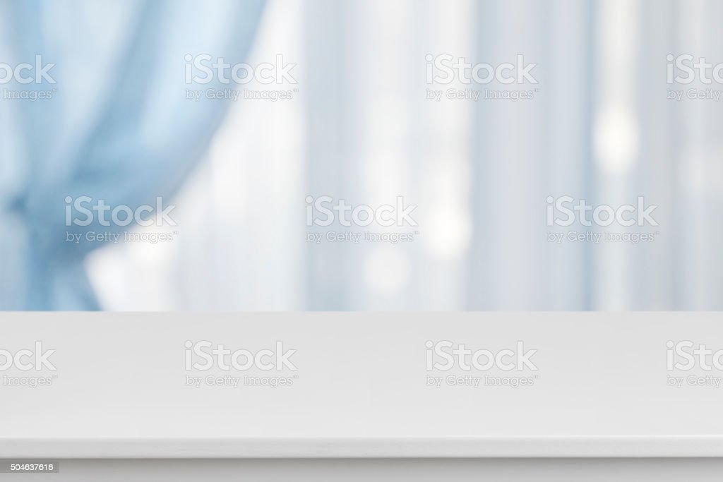 White table on defocuced window with blue curtain background stock photo