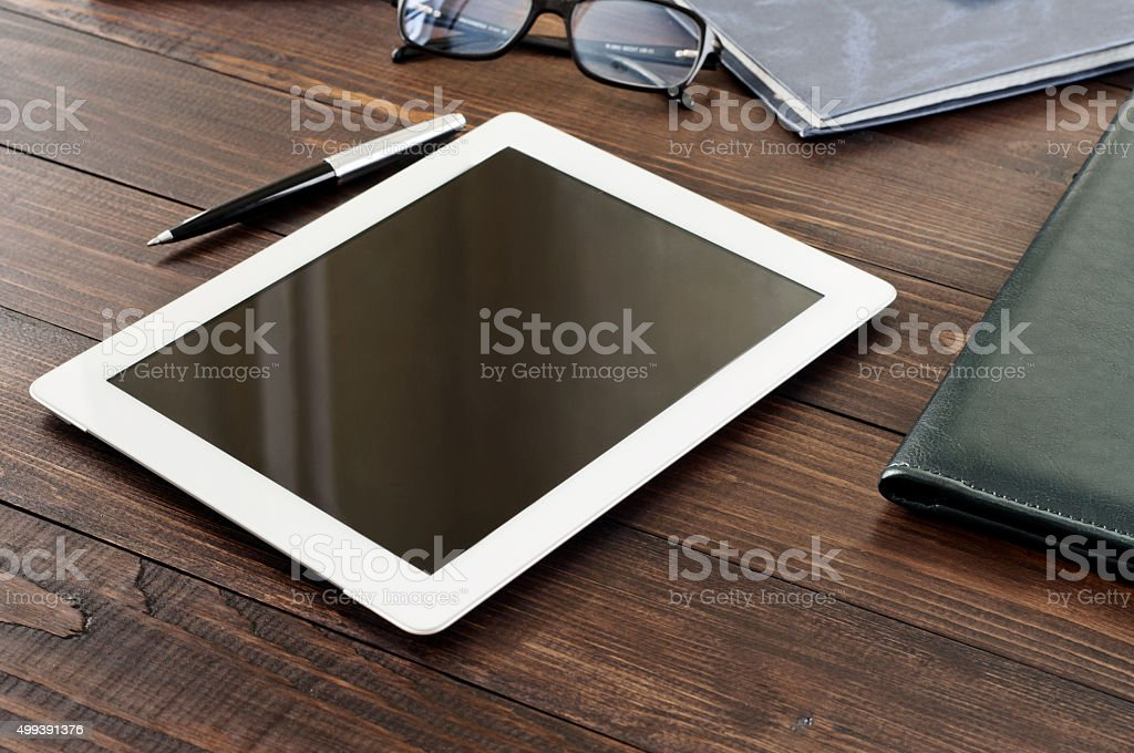 White tablet computer on a wooden table stock photo
