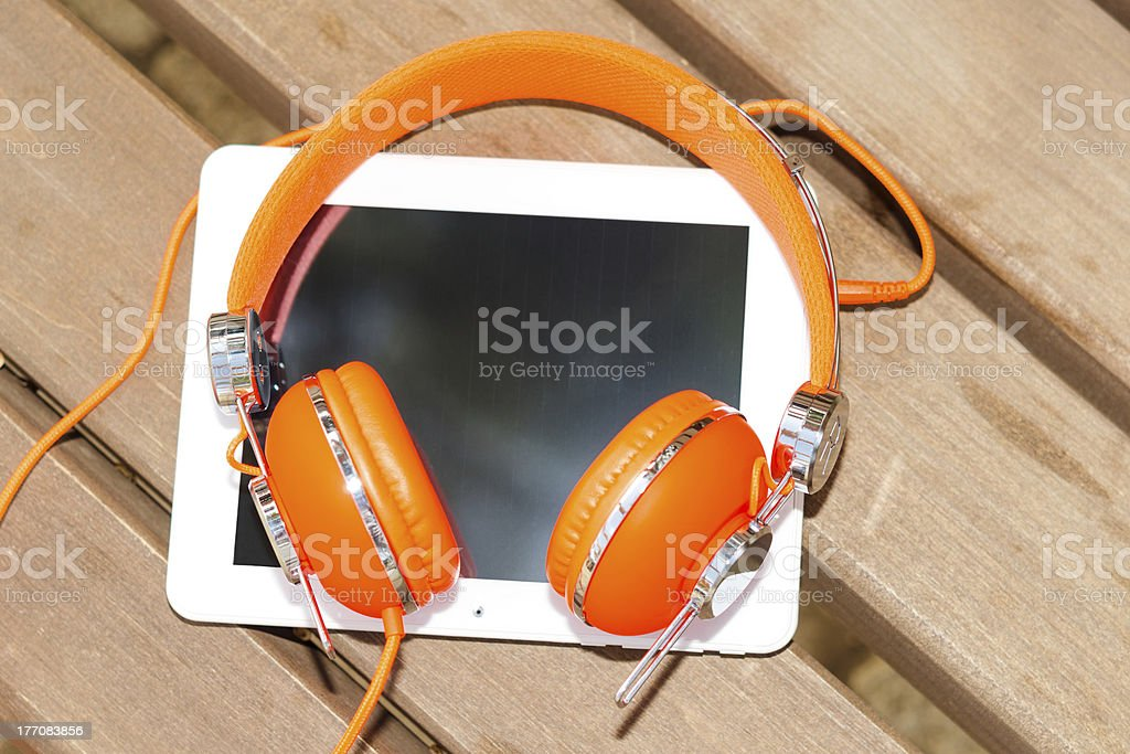White tablet PC with orange headphones on the wood bench royalty-free stock photo