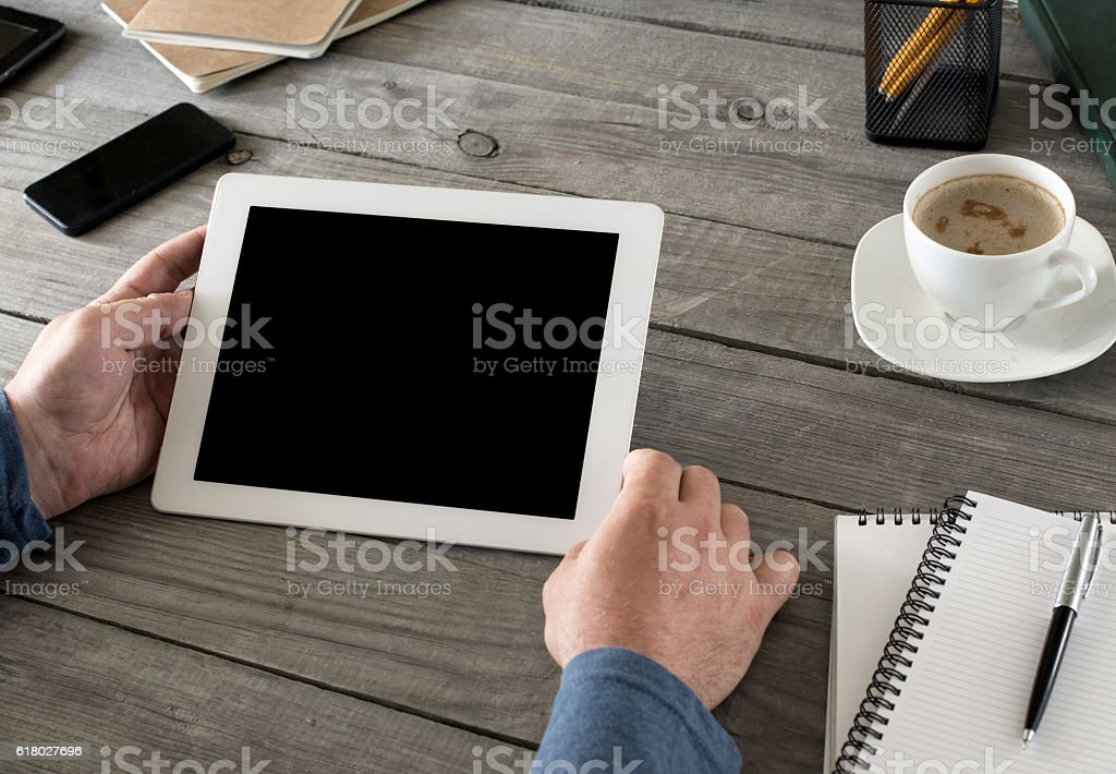 White tablet with blank screen in man hands stock photo