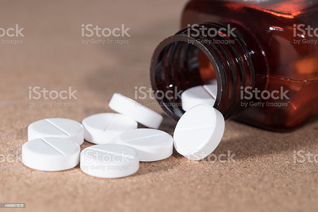 White tablets spilling out of bottle royalty-free stock photo
