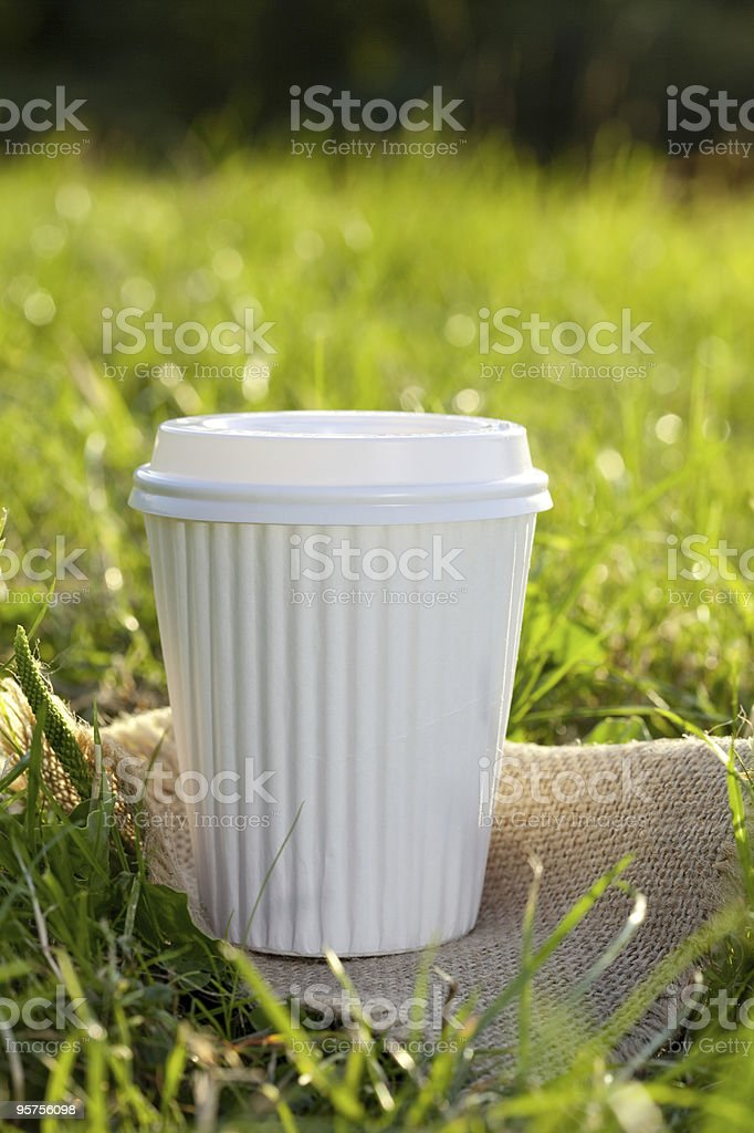 white take out away coffee cup in the grass royalty-free stock photo