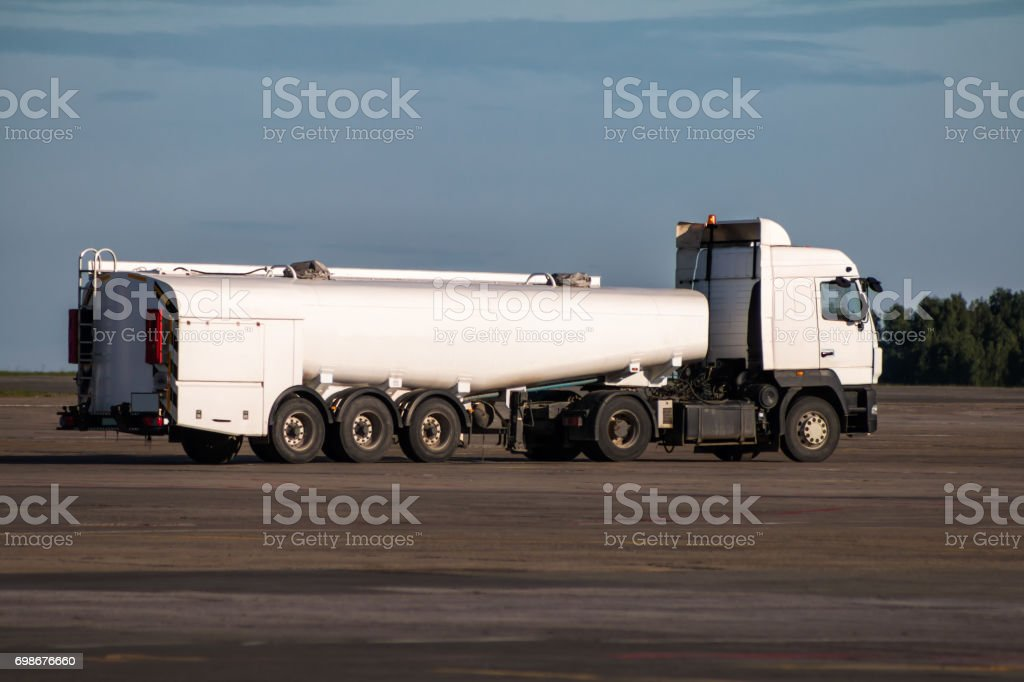 White tank truck aircraft refueler at the airport apron stock photo