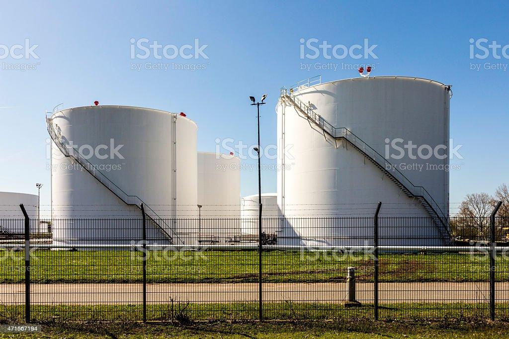 white tanks in tank farm with iron staircase stock photo