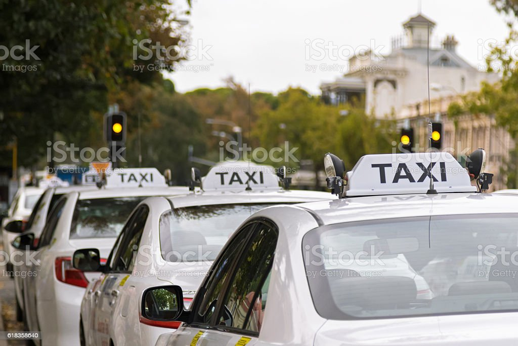 White taxi cars parking along the footpath in Adelaide, Australia stock photo