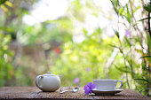 white tea cup with white teapot on wooden table