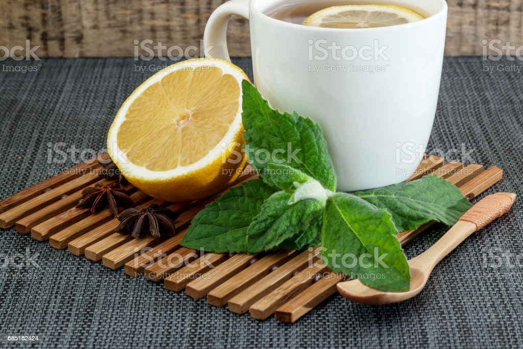White tea mug with lemon and mint leaves and a wooden spoon stock photo