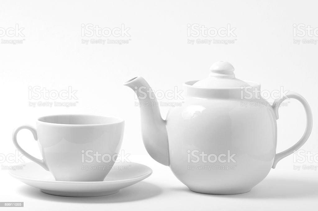 White teacup and saucer next to white teapot stock photo