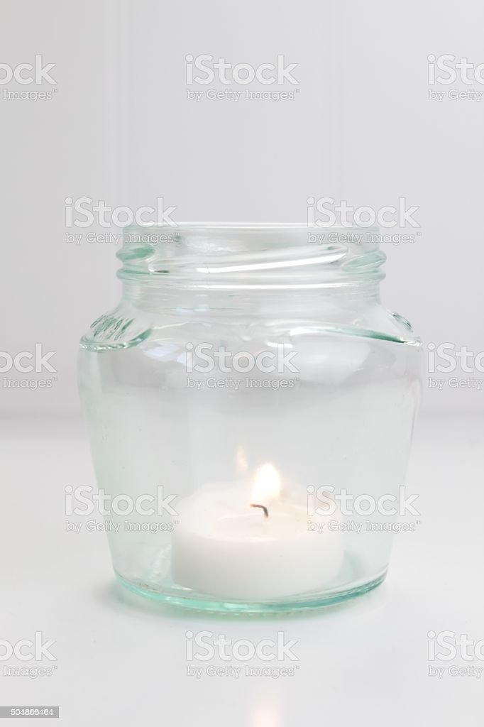 White tealight in a glass jar stock photo