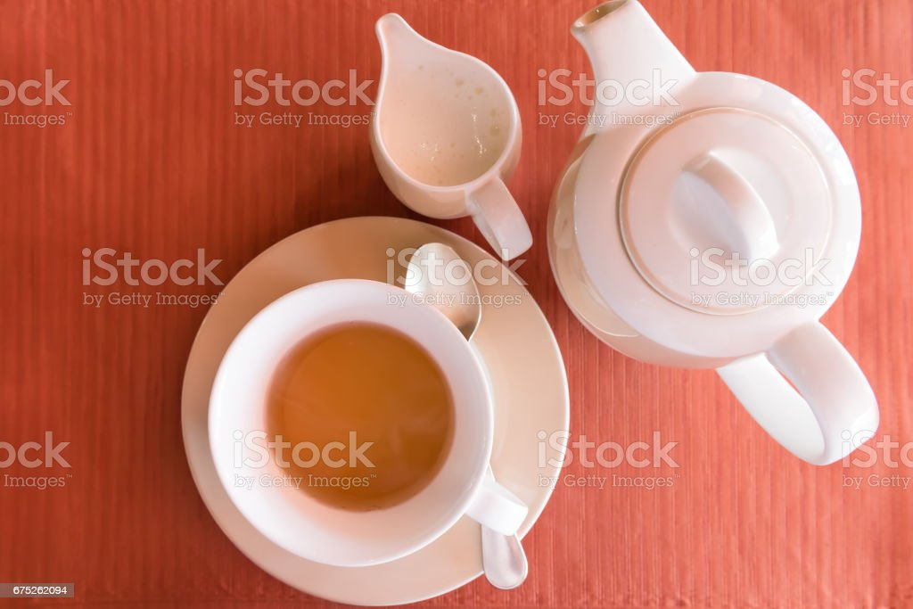 white teapot set on an orange table runner stock photo