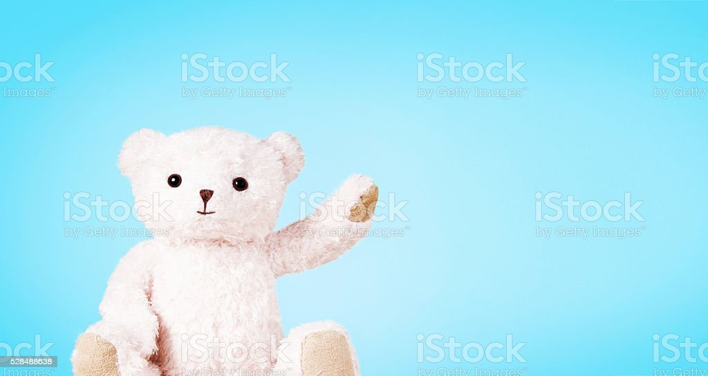 White teddy bear isolated on light blue background. stock photo