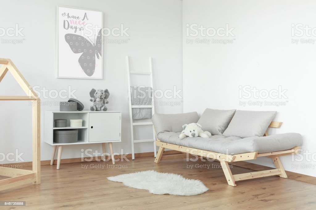 White teddy bear on grey sofa stock photo