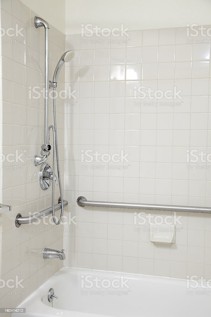 White Tile Bathroom Tub Shower with Grab Bars for Handicapped royalty-free stock photo