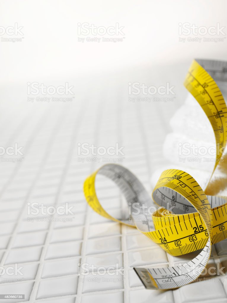 White Tiled Floor with Bath Towels and Tape Measure stock photo