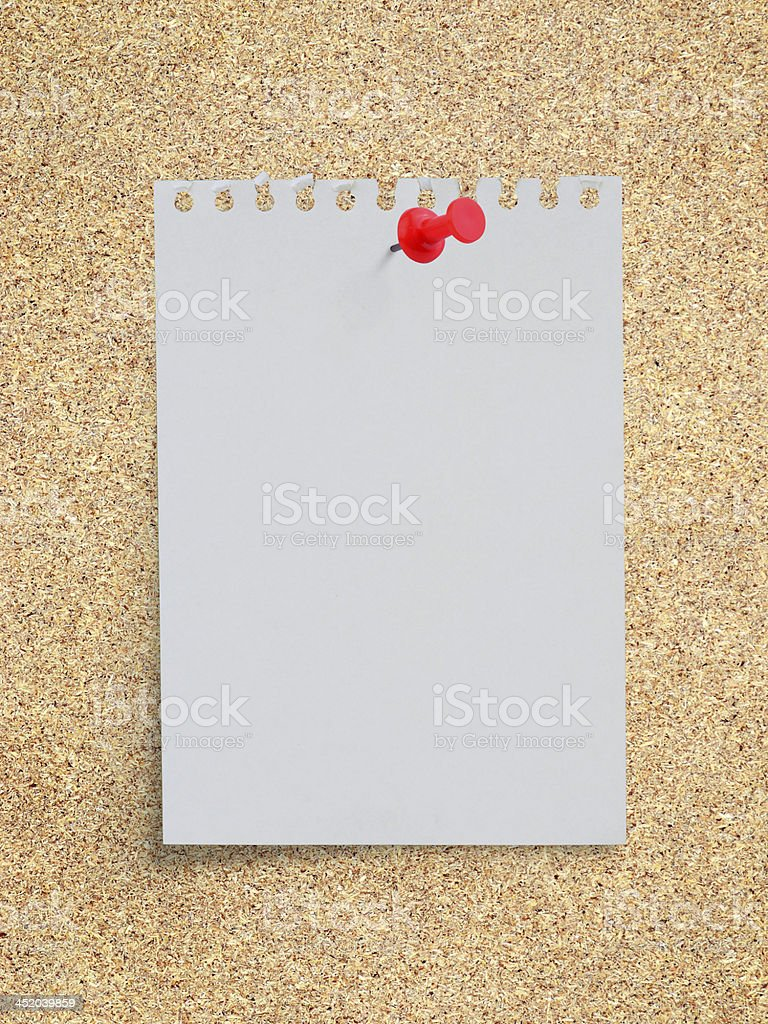 White torn paper note with red pushpin on memo board royalty-free stock photo