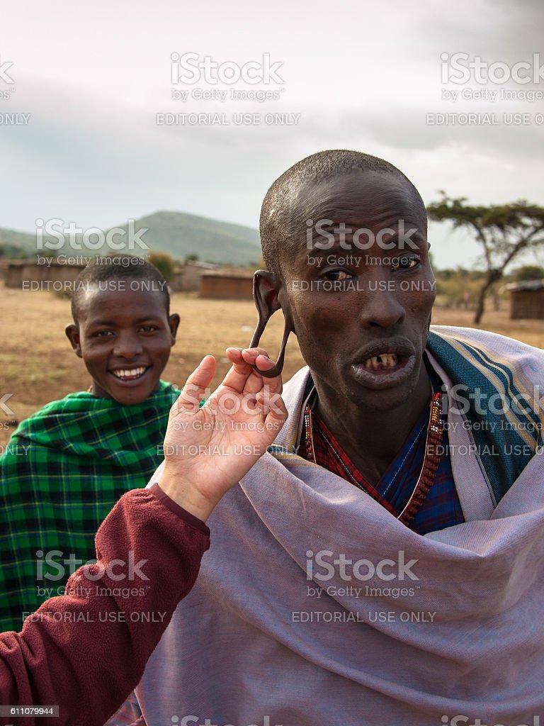 White tourist jokingly checks Masai warrior stock photo