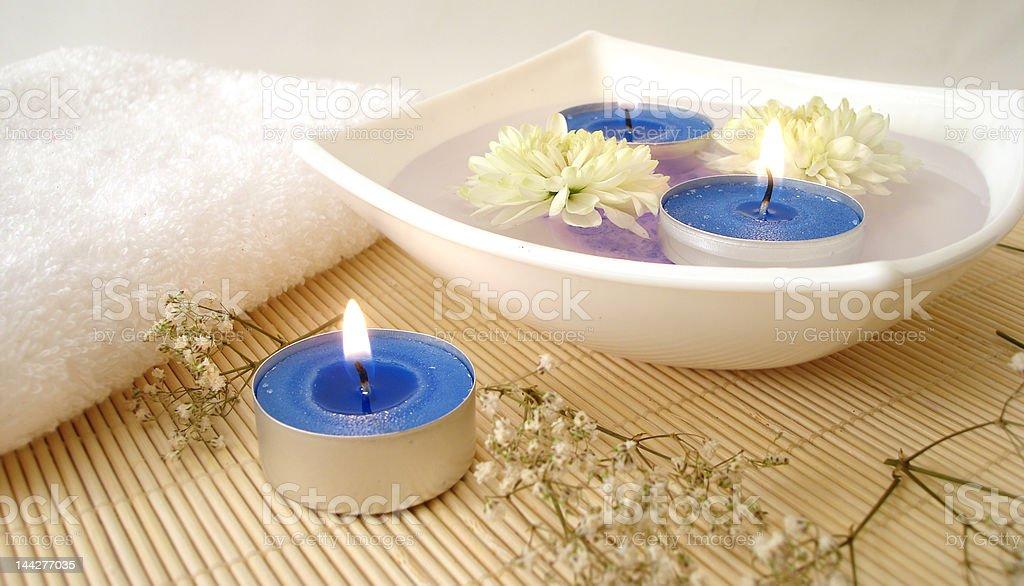 Toalha branca, azul velas e flores em água foto de stock royalty-free