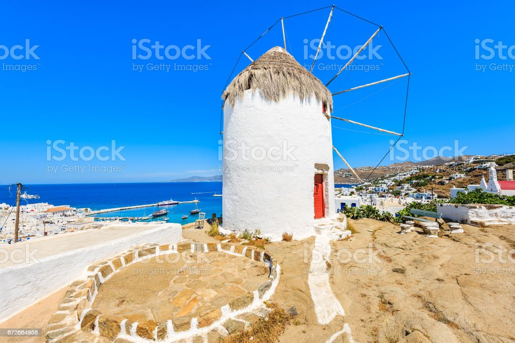 White traditional windmill overlooking Mykonos port, Cyclades islands, Greece stock photo