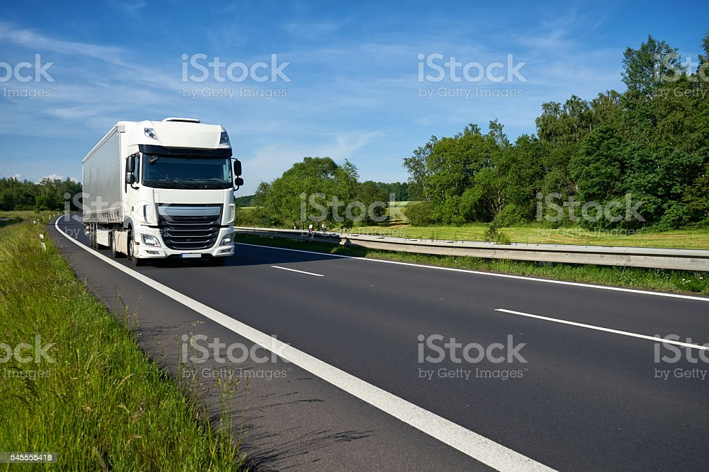 White truck arriving on the highway lined with leafy trees. stock photo