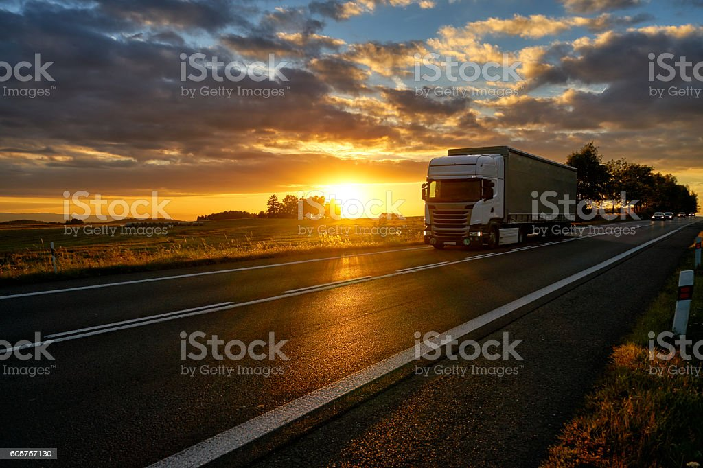White truck driving on asphalt road during a dramatic sunset. stock photo