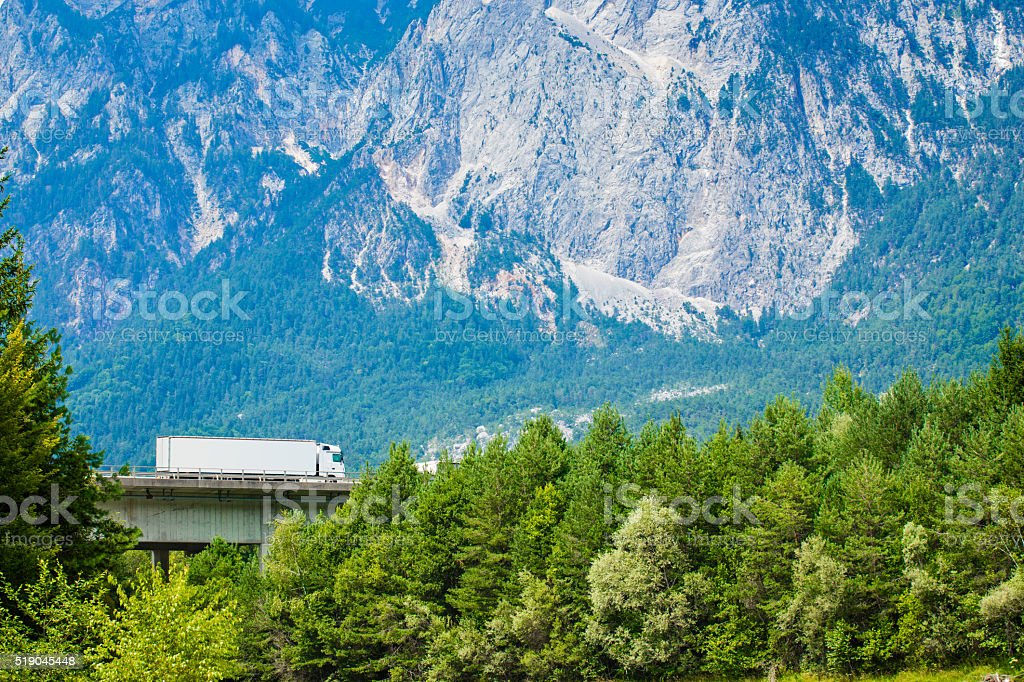 White Truck on the highway in European Alps. stock photo