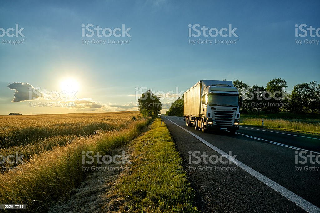 White truck on the road along the field at sunset. stock photo