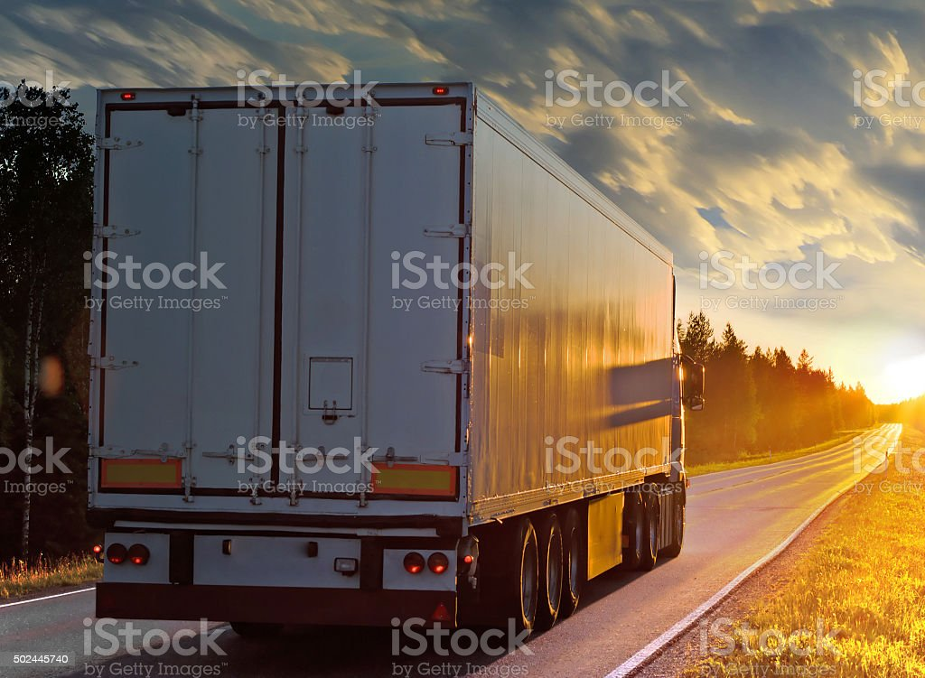 White truck on the rural road in evening stock photo