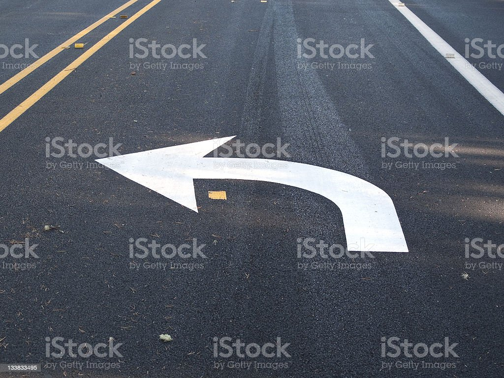 White turn left arrow painted on asphalt stock photo