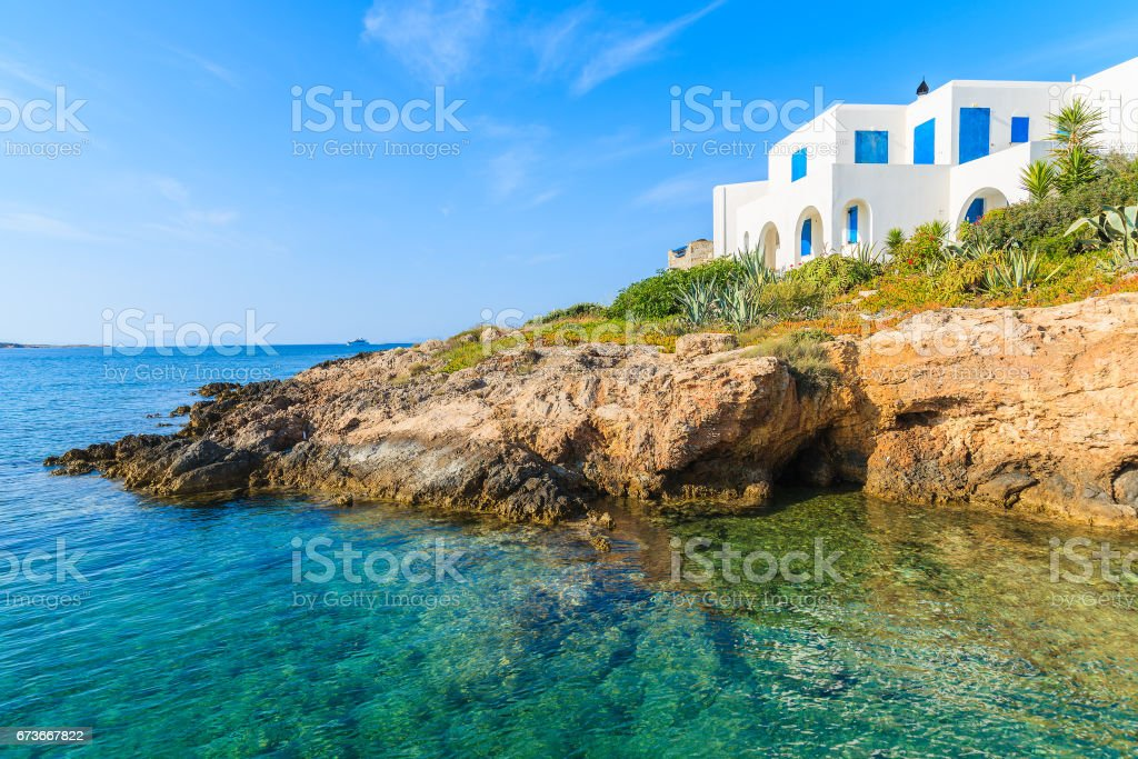 A white typical Greek house on cliff overlooking beautiful sea cove with crystal clear, Naoussa village, Paros island, Cyclades, stock photo