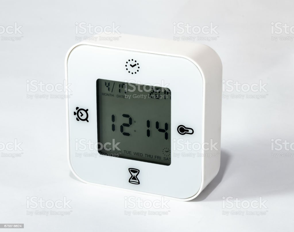 White universal desk clock alarm clock, also showing days of the week, date, stopper and temperature on white background stock photo