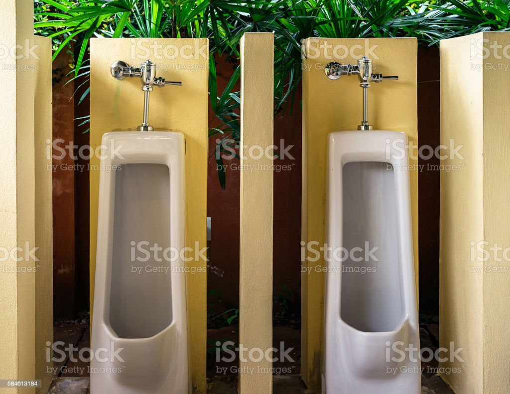 White urinals against yellow wall in toilet photo libre de droits