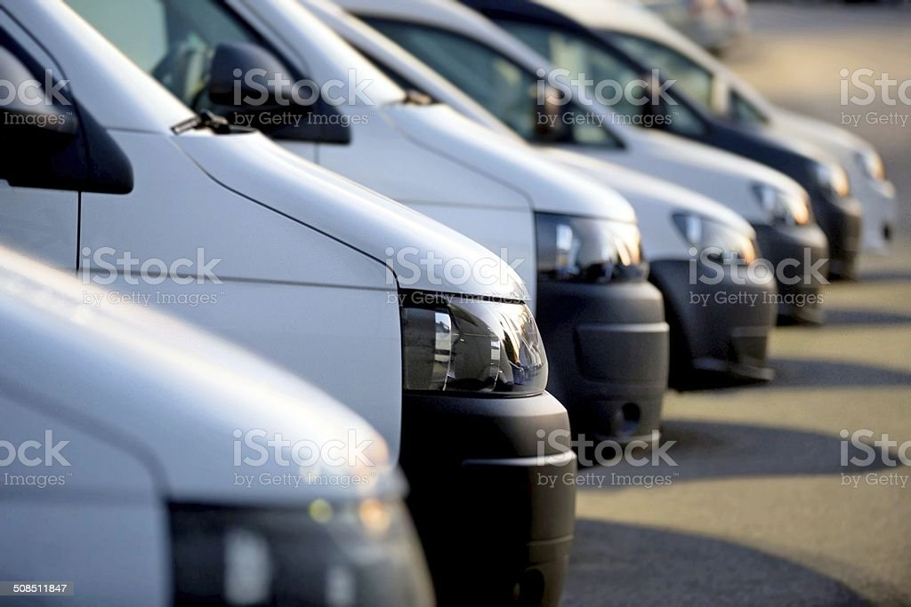 White vans in a row at dusk stock photo