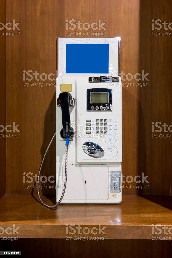 White vintage public pay phone stock photo