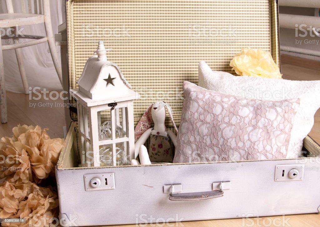 white vintage suitcase lies toy rabbit, is a white lamp stock photo