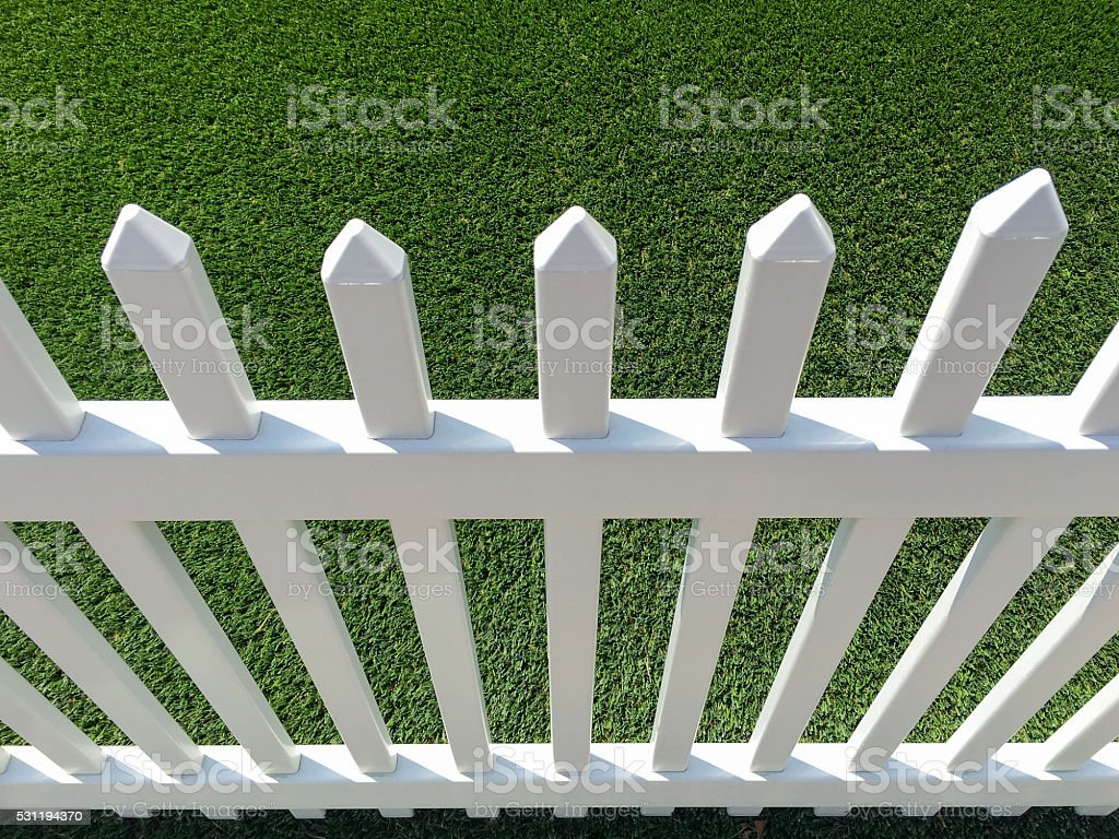 White vinyl picket fence and green synthetic grass stock photo