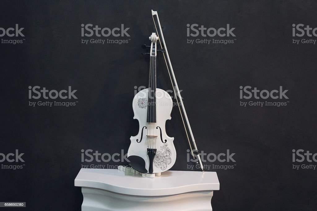 White violin on a pedestal on a black background. Music stock photo