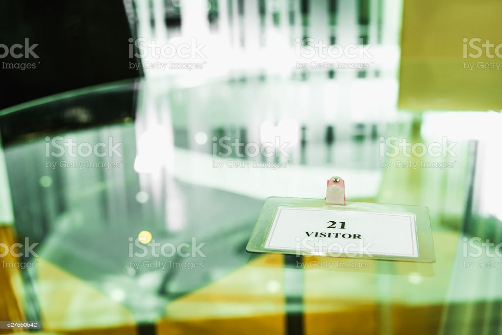 White visitor plastic card on glass table stock photo