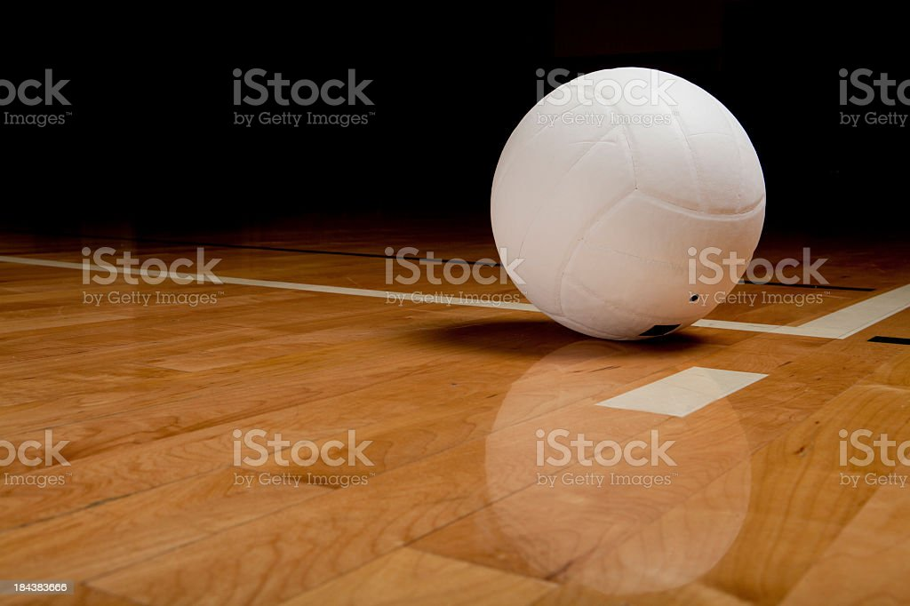 A white Volleyball on a hardwood floor stock photo