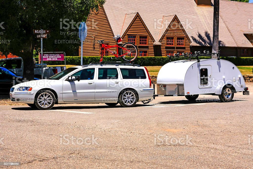 White Volvo Stationwagon towing a travel trailer stock photo