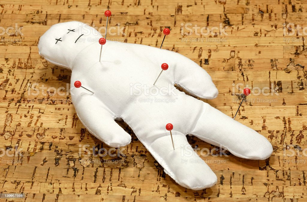 A white voodoo doll with five red pins in it stock photo