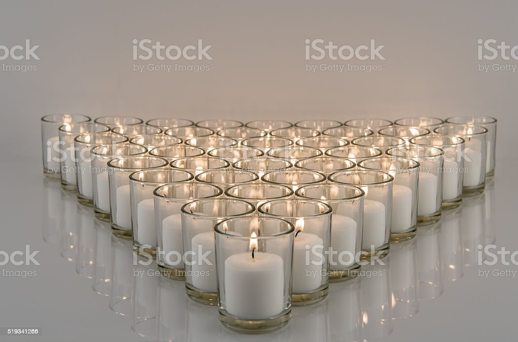 White Votive Candlelight on Reflective Surface stock photo
