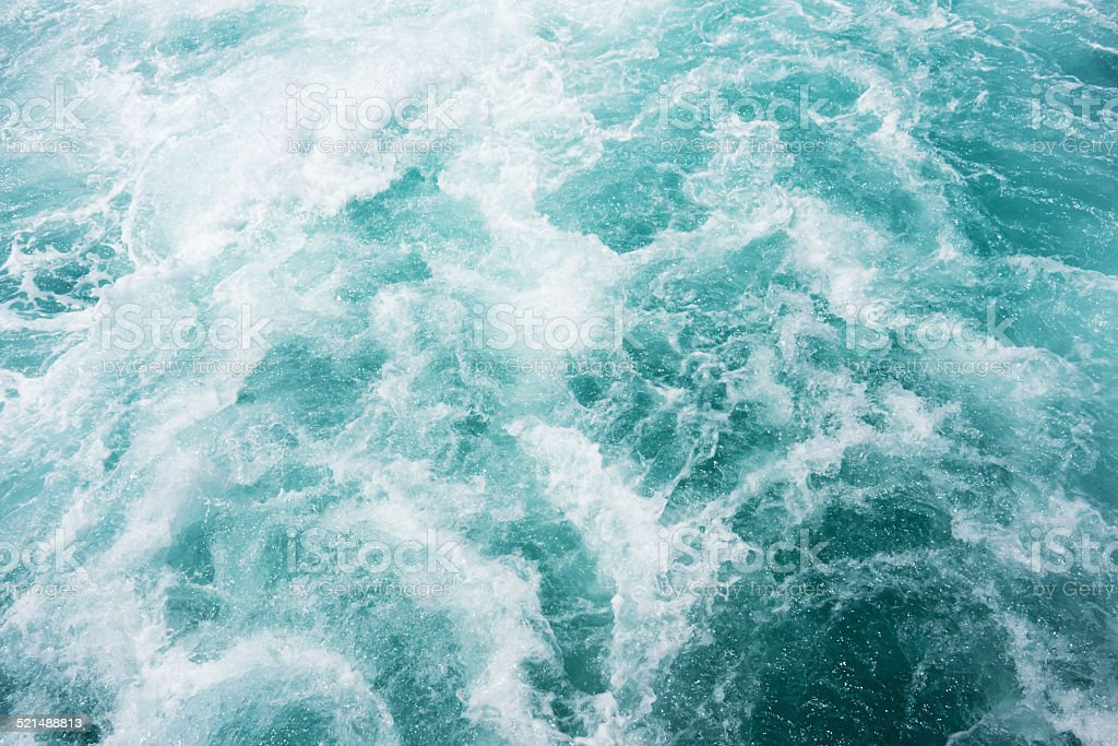 white wake on the blue ocean stock photo