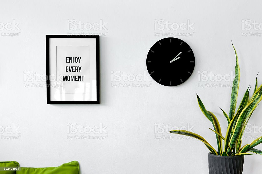 White wall decoration with a picture frame, clock and plants stock photo