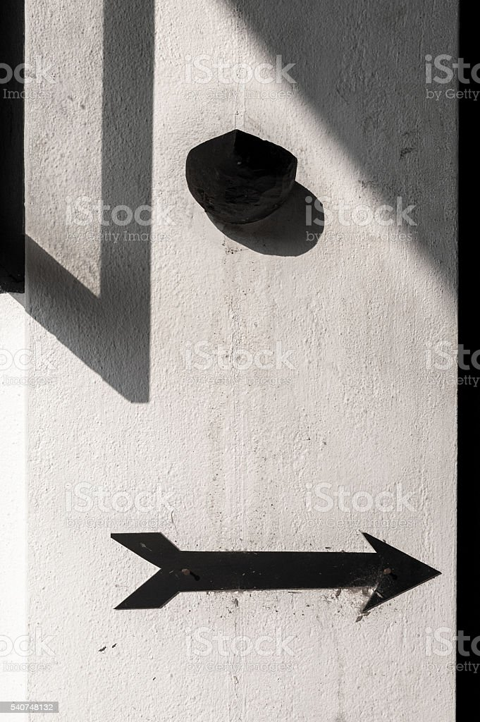 White wall detail with black arrow and geometric shadows stock photo