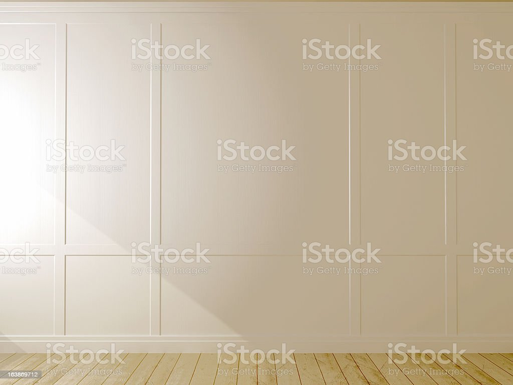 A white wall with elevated sections atop a wooden floor stock photo