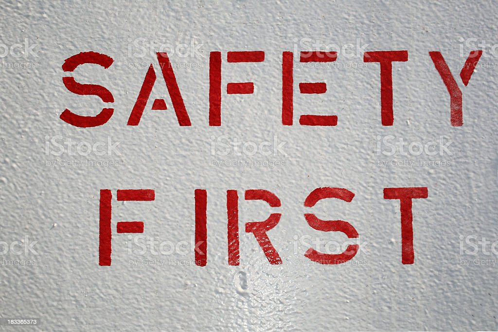 White wall with red safety first painted on stock photo